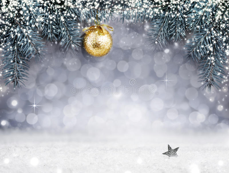 Christmas background with snow and golden ball on spruce branch. stock image