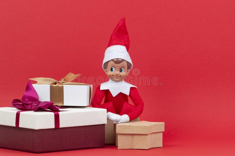Christmas background. Stack of Xmas present boxes and sitting toy elf on red background royalty free stock images