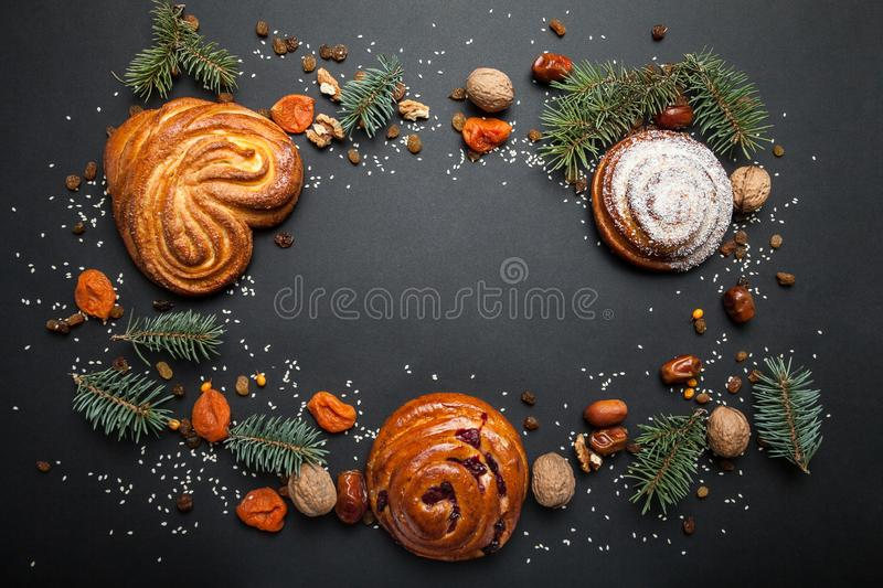 Christmas background of sweet baked goods, nuts and dried fruits with Christmas tree and decorations on a dark background.  royalty free stock photo