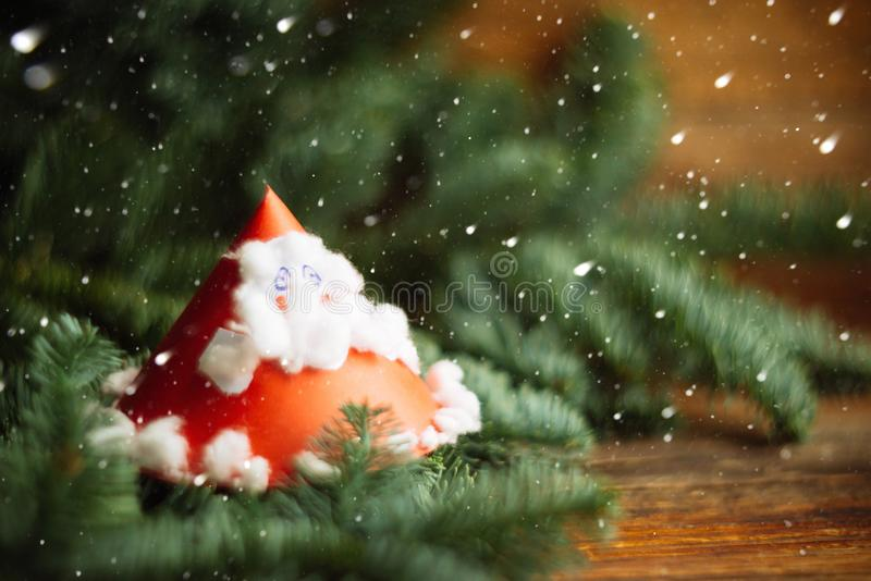 Child's painting of Santa Claus with bag. Christmas background, texture, substrate, layout: children's crafts from paper - Santa Claus with fir branches royalty free stock photo