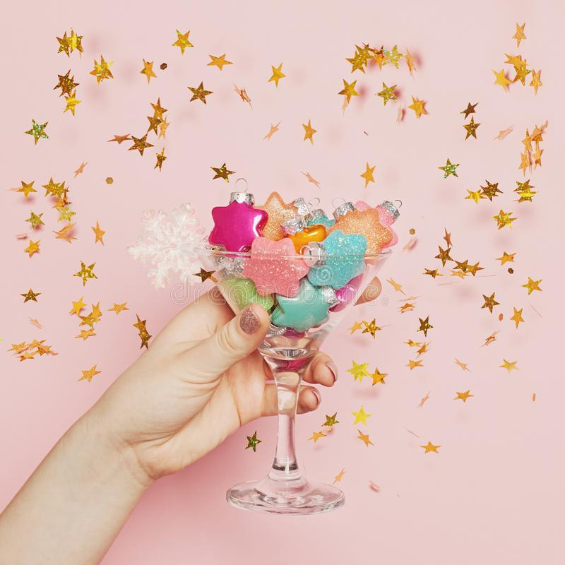 Christmas background, toast and chin-chin concept. Xmas glass with decoration in hand on pink background with gold glitter sparkle stock photos