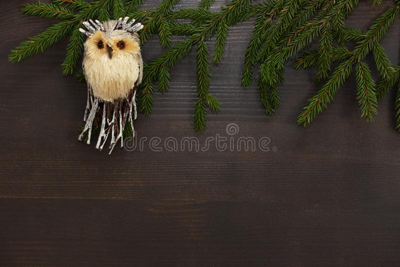 Christmas background. A toy owl with green fir branches on a wooden brown background. Christmas toy.Frame for Christmas text. Top stock images