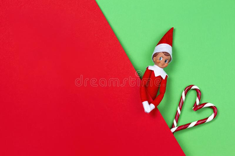 Christmas background. Toy santa elf and candy canes on red and green background. Top view stock photography
