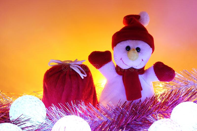 Christmas background. Toy snowman and a red bag with gifts among tinsel and Christmas light balls. Christmas background with empty space. Toy snowman and a red royalty free stock photo