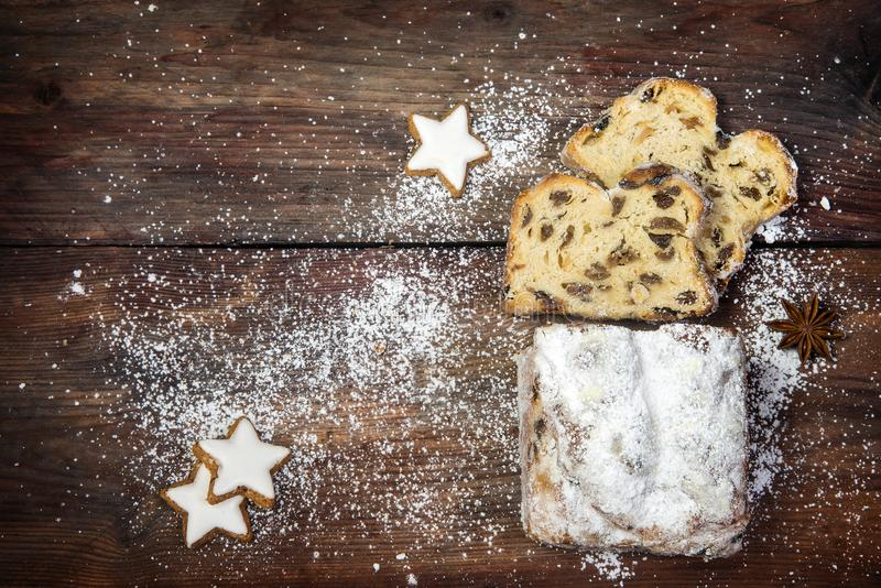 christmas background, traditional german criststollen cake sprinkled with icing sugar, cinnamon cookies and anise stars on a dark stock photo