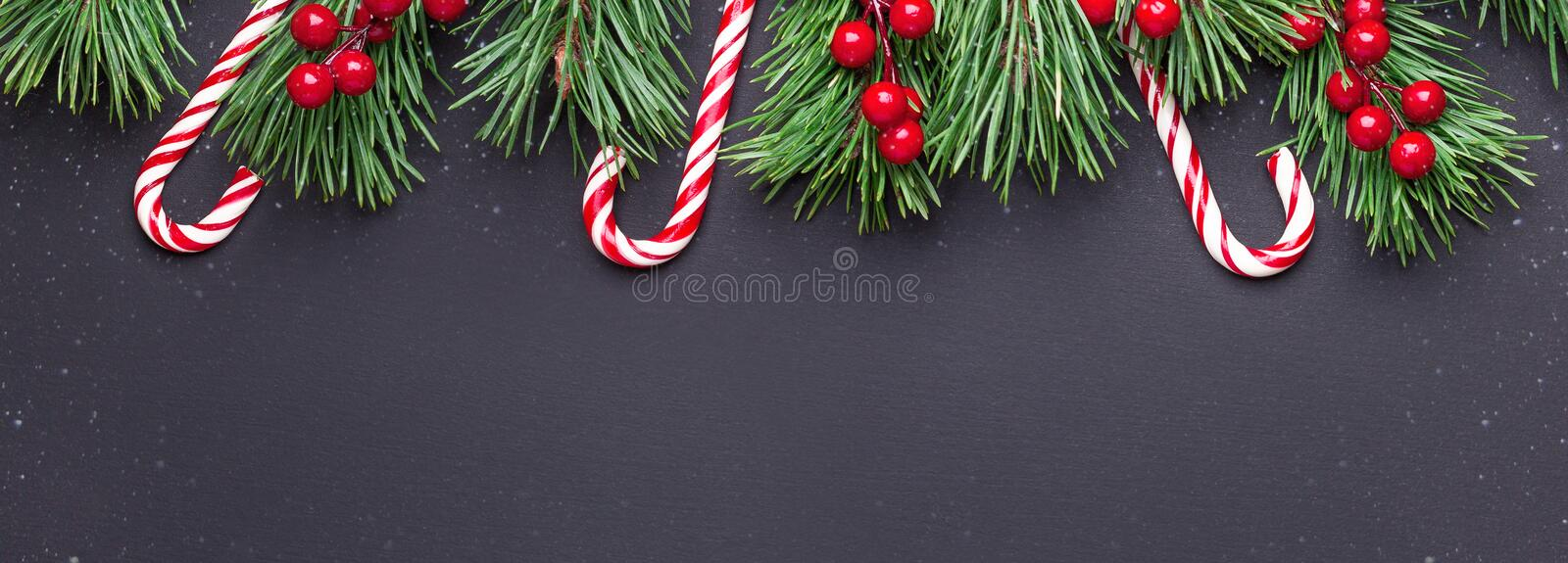 Christmas background with tree branches, candy cane and holly on black wooden background. Snowfall drawing effect. Horizontal banner. Top view Copy space stock photo