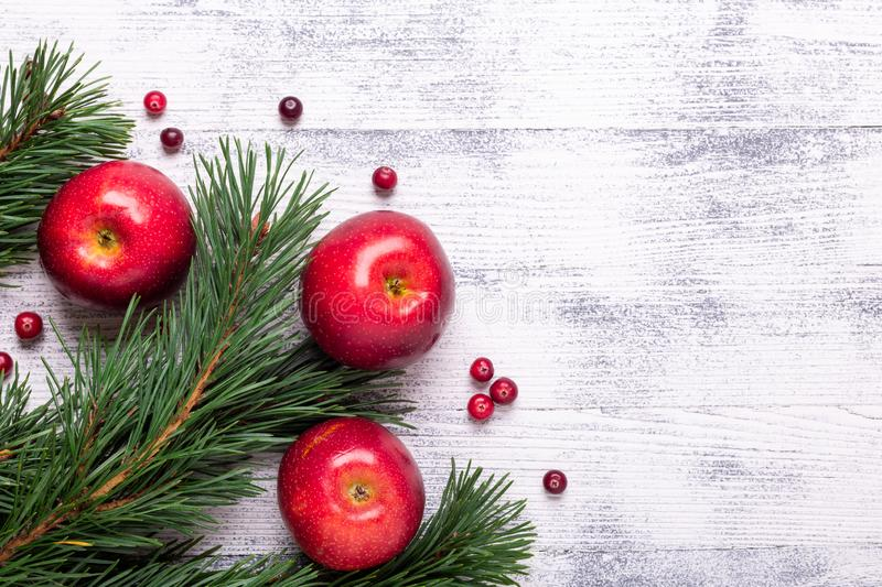 Christmas background with tree branches, red apples and cranberries. Light wooden table stock photos