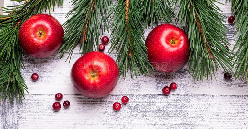 Christmas background with tree branches, red apples and cranberries. Light wooden table royalty free stock photos