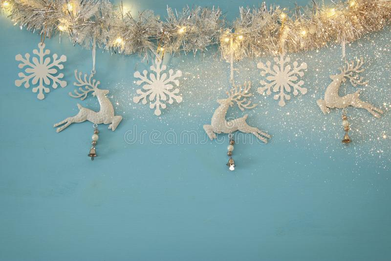 Christmas background with tree festive garland, white deer, and paper white snowflakes over light blue background. royalty free stock photo