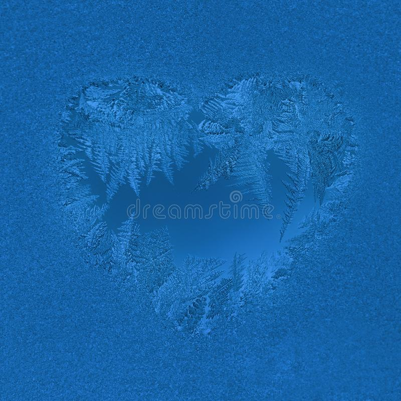 Christmas background in trendy color 2020 Classic Blue. Frosty window pattern in heart shape. Selective focus. Christmas natural background in trendy color 2020 stock photo