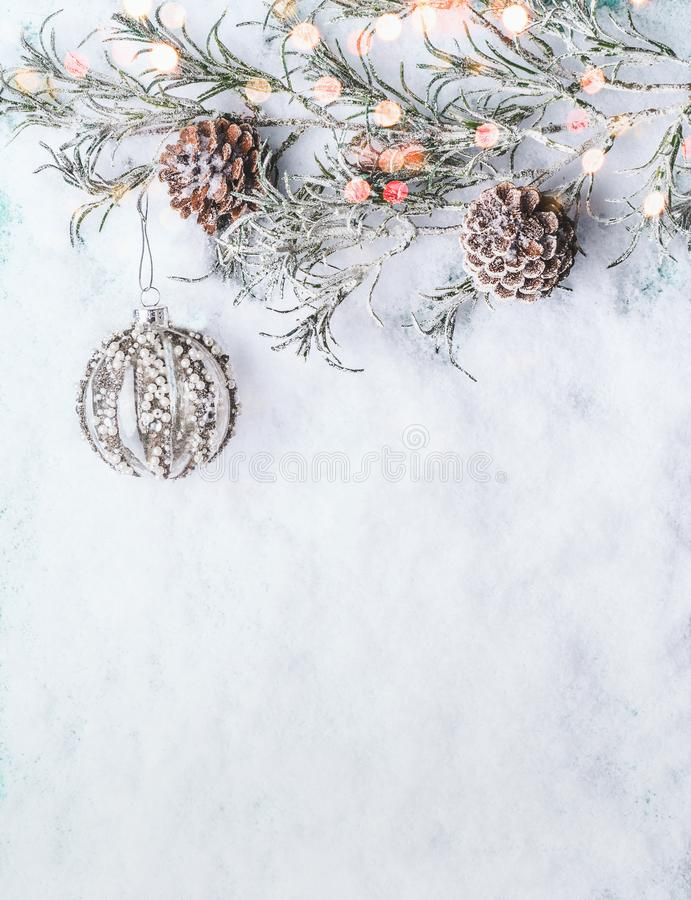 Christmas background with vintage bauble , frozen branches and cones on snow with bokeh. Top view with copy space for your design, border stock image