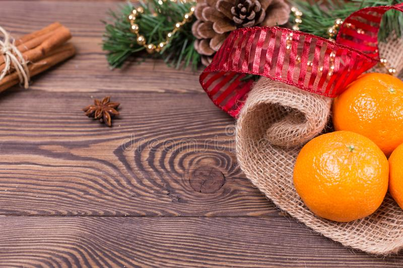 Christmas background - vintage wood, cinnamon, star anise, sweet mandarins, a New Year`s decor.Top view, blank space stock photo