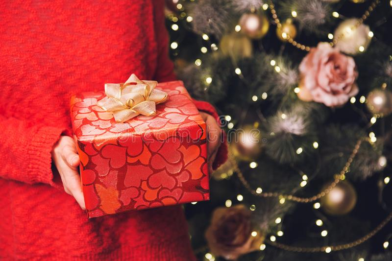 Woman`s hands holding Christmas or New Year decorated gift box. royalty free stock image