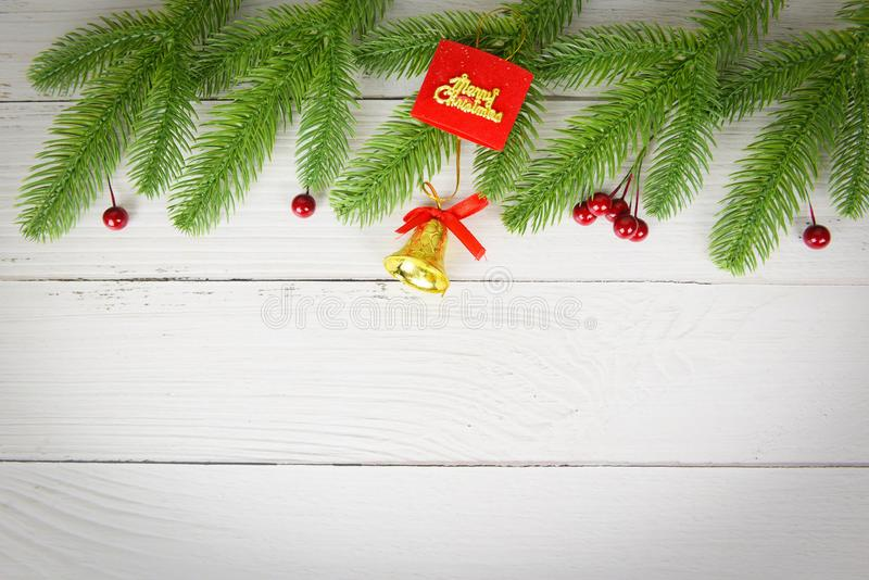 Christmas background wood composition fir branches and red berries / christmas decoration pine tree with bell festive xmas winter. And Happy New Year object royalty free stock photo