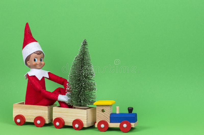 Christmas background. Wooden toy train with sitting toy elf and small Xmas fir tree on light green background stock image