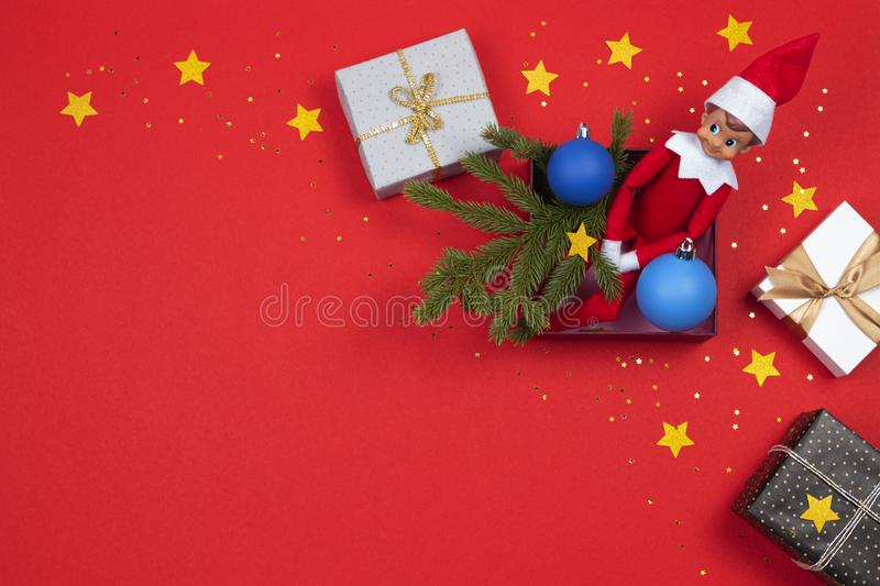 Christmas background. Xmas present boxes, little toy Santa elf, green fir branches and decoration baubles on red royalty free stock image