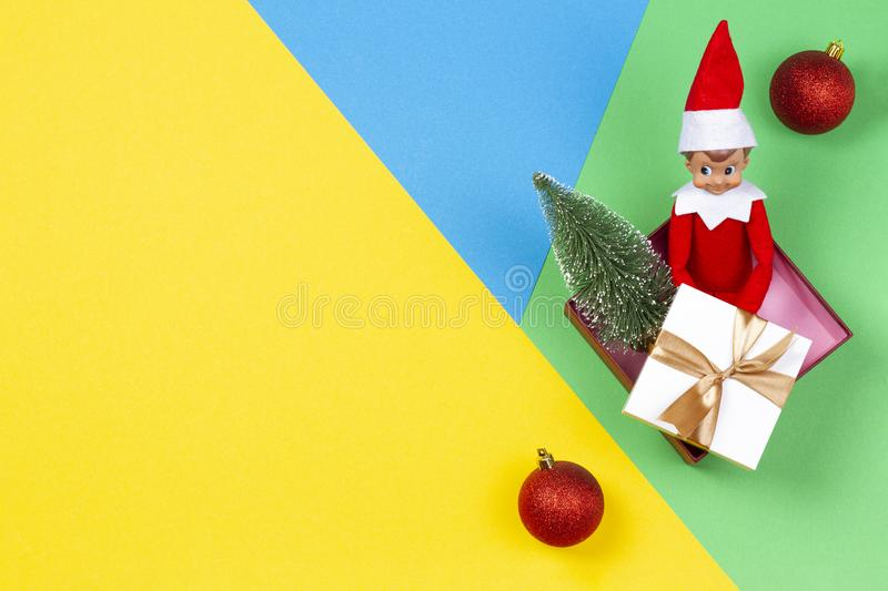 Christmas background. Xmas present, decoration and toy elf on yellow, green and blue background stock photography