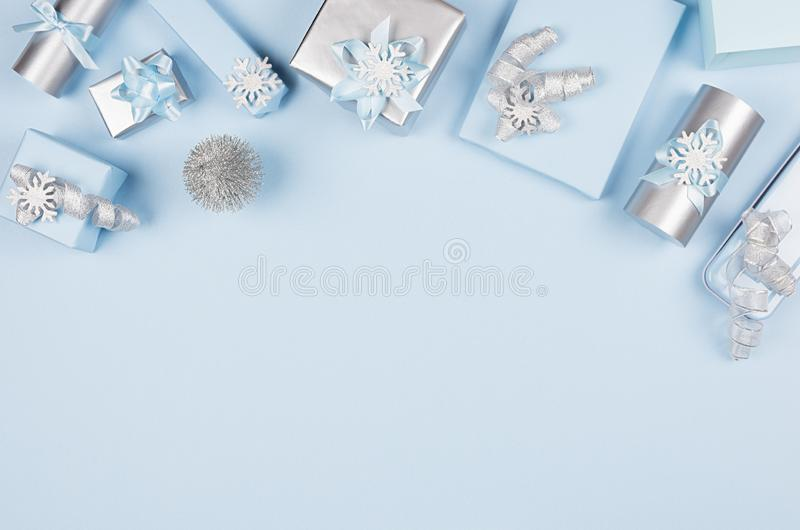 Christmas background for your design and text - soft pastel blue and silver gift boxes with bows, christmas tree on blue backdrop. Christmas background for your stock image