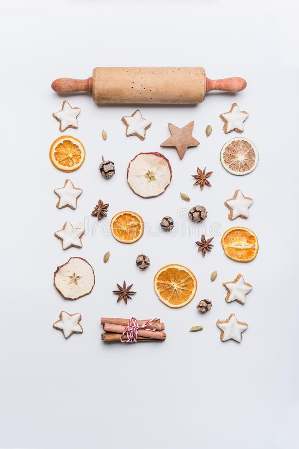 Christmas bake flat lay composition with rolling pin, star cookies , dried fruits and spices on white background, top view. Festive layout or pattern for stock photos