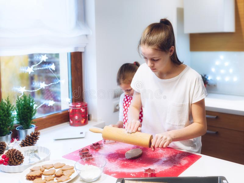 Christmas bakery. Two sisters making gingerbread, cutting cookies of gingerbread dough. stock image