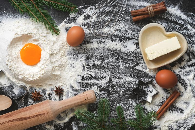Christmas baking background, flour, butter, eggs decorated with spruce twigs. Top view, copy space royalty free stock images