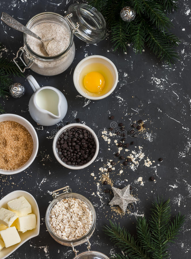 Christmas baking background. Flour, sugar, butter, rolled oats, eggs, chocolate chips on a dark background. stock photography