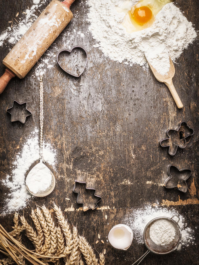 Christmas baking background with ingredients and tools: Cookie Cutters, Cups, Mats, Rolling Pin, spoon . Dark, rustic, top view, frame royalty free stock photos