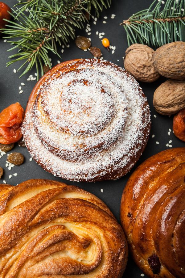 Christmas baking background. Sweet buns with spices and ornaments on a black background.  royalty free stock photography