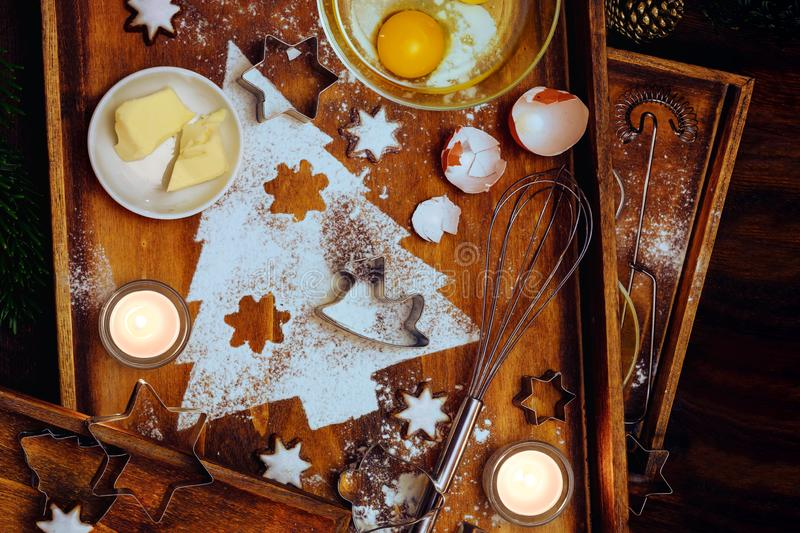 Christmas baking composition, fir tree shape from flour, butter, egg and cinnamon stars, utensils and candles on warm brown wooden. Trays, flat lay, high angle stock image