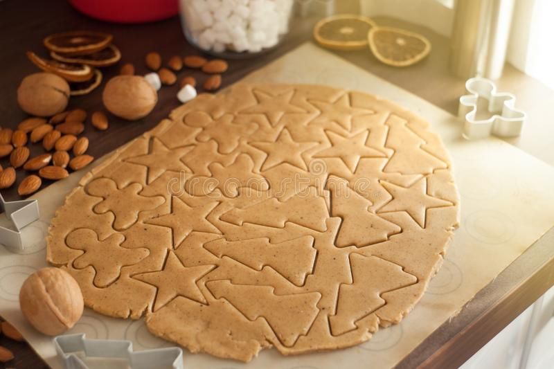 Christmas baking. Ginger dough for gingerbread, gingerbread men, stars, Christmas trees, spices. On the home kitchen wooden table. royalty free stock image