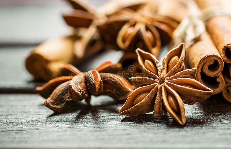 Christmas Baking Ingredients Cinnamon Sticks Anise Star Cloves Cardamom Scattered on Wood Background. royalty free stock photography