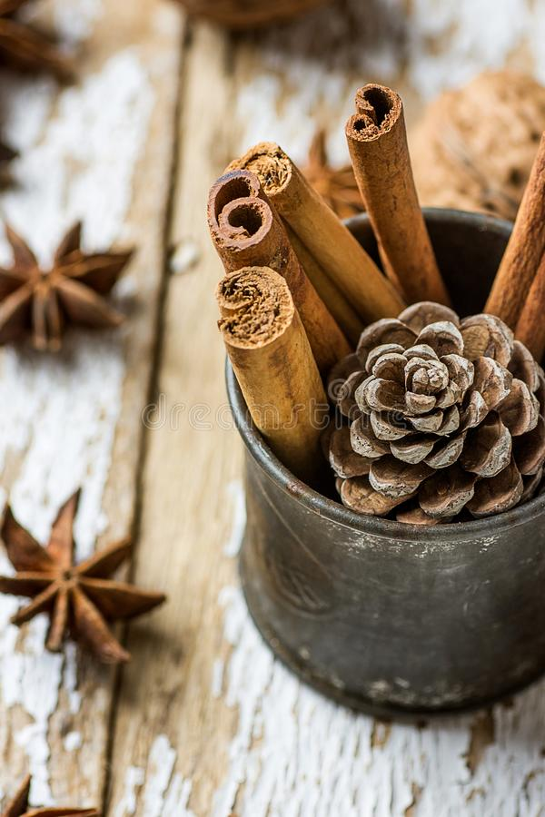 Christmas Baking Ingredients Cinnamon Sticks Scattered Anise Star Walnuts Pine Cone in Vintage Jug on Wood Background. Postcard royalty free stock photography