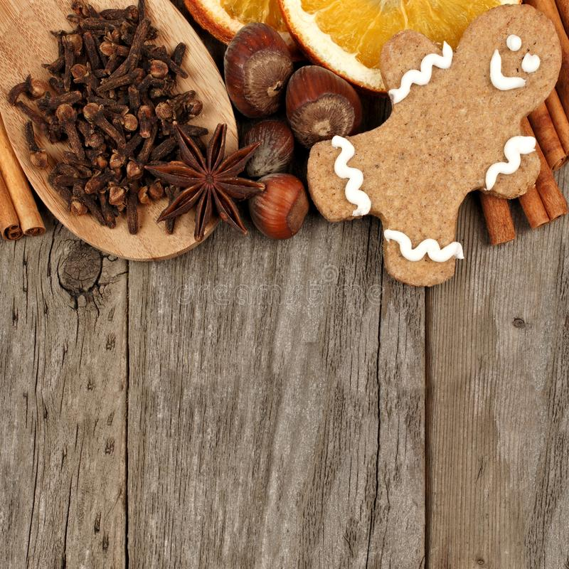 Christmas baking ingredients and gingerbread man border over rustic wood. Top border of Christmas baking ingredients with gingerbread man over a rustic wood stock images