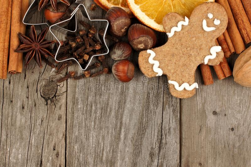 Christmas baking ingredients and gingerbread man border on rustic wood. Top border of Christmas baking ingredients with gingerbread man over a rustic wood stock image