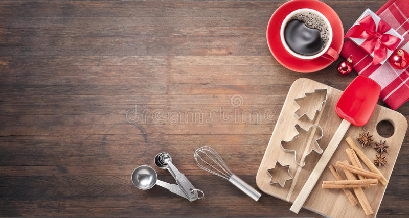 Christmas Baking Cookies Wood Background. Various baking utensils, cookie cutters, spices, present, and christmas ornaments on a rustic wood background