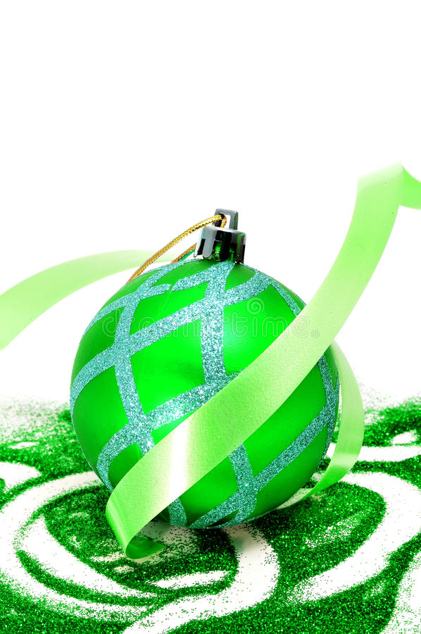 Christmas ball. Green christmas ball with green glitter and green ribbon on a white background stock photo