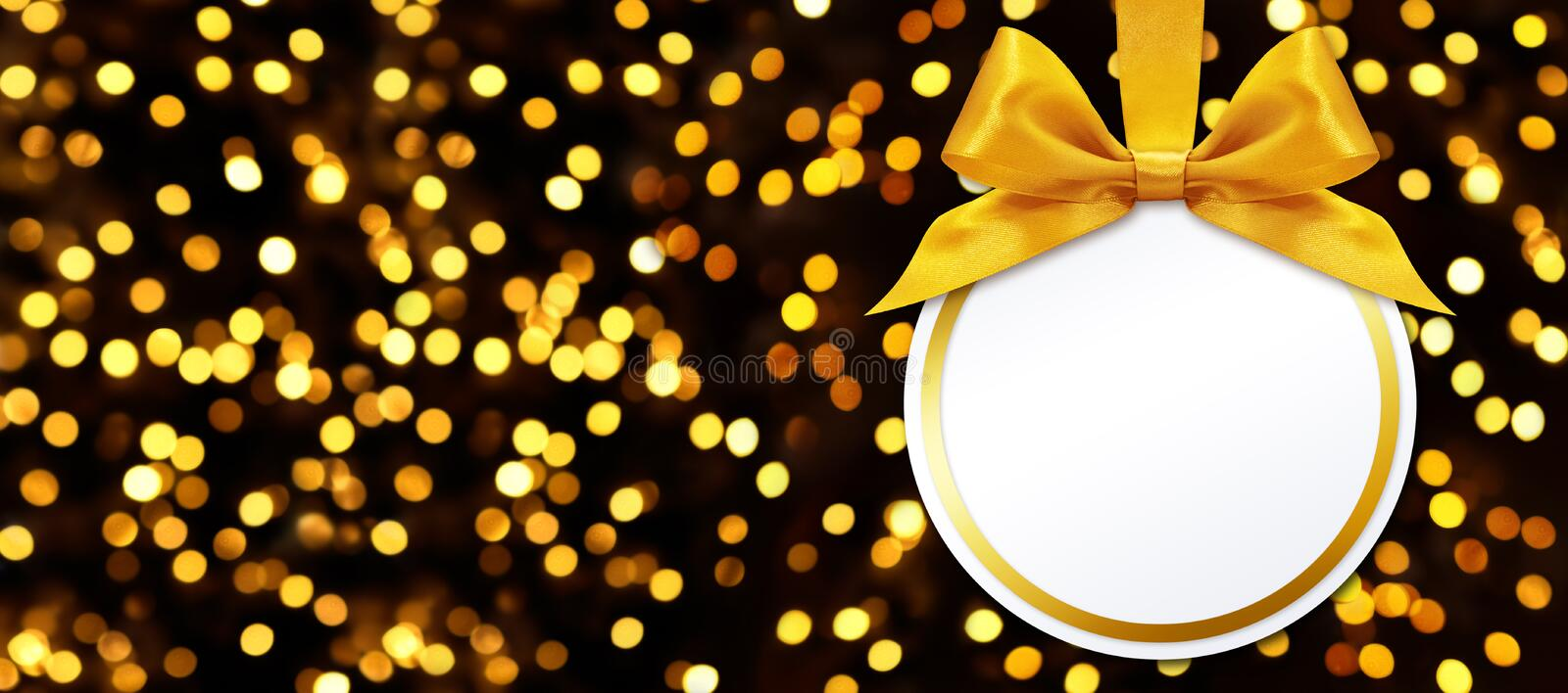Christmas ball with bow hanging on lights background. Christmas ball with bow hanging on lights glitter background royalty free stock image