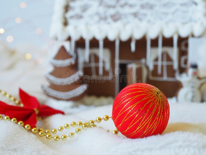 Christmas ball in front of a gingerbread house in the background. Christmas scenery, beautiful decoration stock image