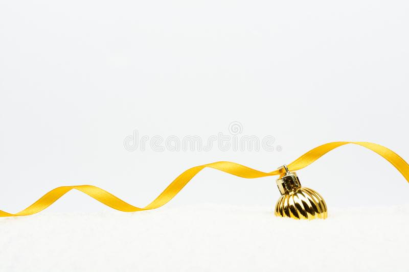 Christmas ball with golden ribbon on artificial snow stock image