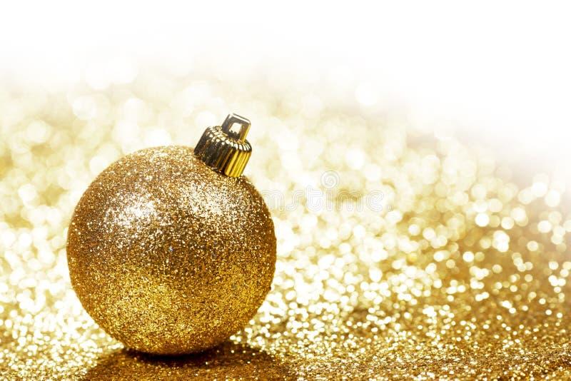 Christmas ball. Golden christmas ball on shining glitter background close-up royalty free stock image
