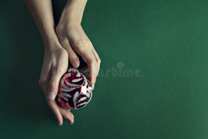 Christmas ball holded in a beauty hands. With a free space on the right royalty free stock image