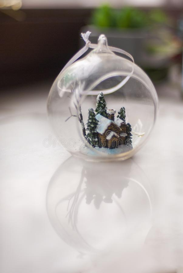 Christmas ball with a house. Beautiful glass Christmas ball with a small house inside it royalty free stock image