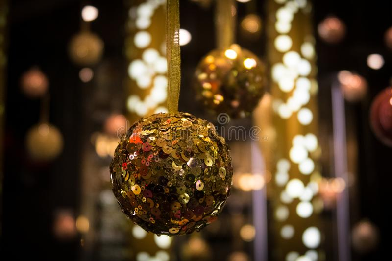 Christmas ball with lights in the background. Golden colored Christmass ball hanging down with lots of reflective lights in the back royalty free stock images