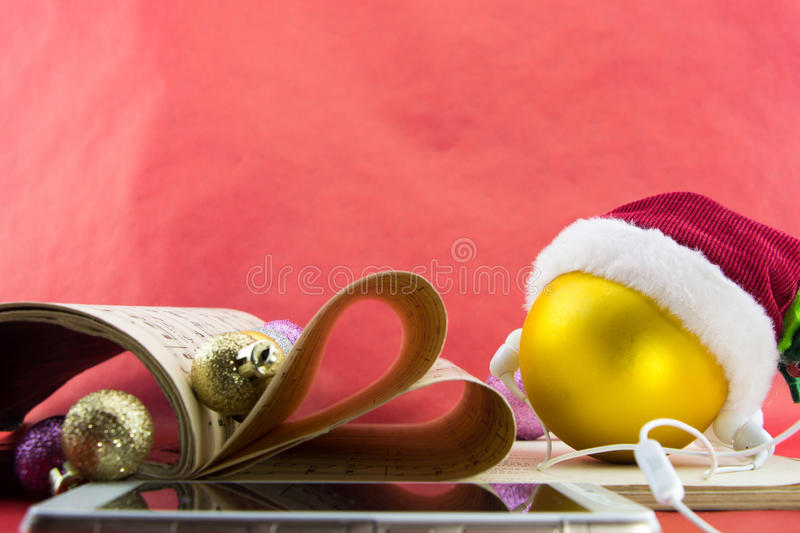 Christmas ball with Santa's hat and earphones, music notation book with pages shaping heart. On red background stock image