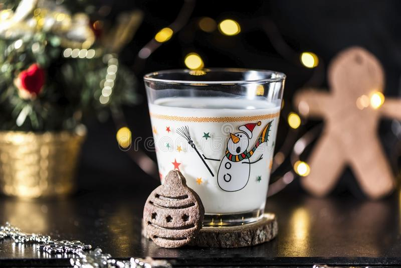 Christmas ball shaped cookie and a glass of milk for Santa Claus, close up, indoor stock photos