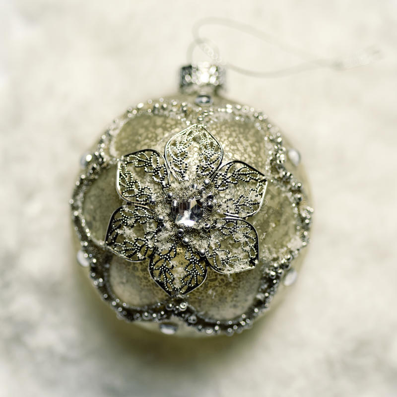 Christmas ball on the snow. High-angle shot of an elegant ornamented christmas ball on the snow stock photography