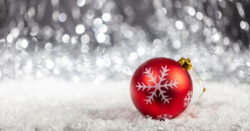 Christmas ball and snow in the night, abstract bokeh lights background. Copy space stock photo