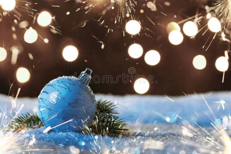 Christmas ball with sparklers and garlands on the snow royalty free stock photo