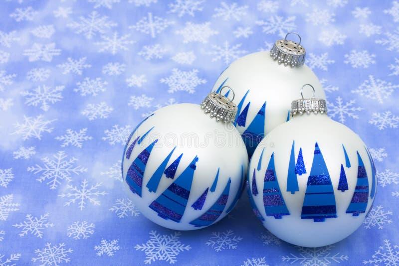 Christmas Balls. White glass Christmas balls with blue trees on them on snowflake background, Christmas balls stock images