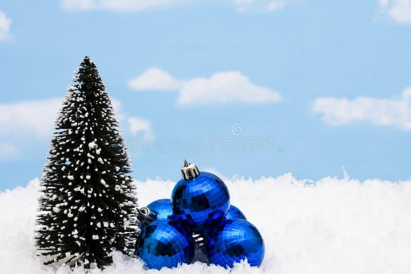 Christmas Balls. Blue Christmas balls with tree on snow royalty free stock photography